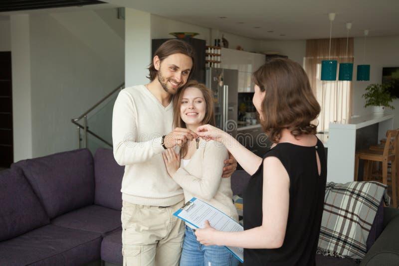 Arrendatarios jovenes felices de los pares que consiguen llaves del nuevo hogar de alquiler imágenes de archivo libres de regalías