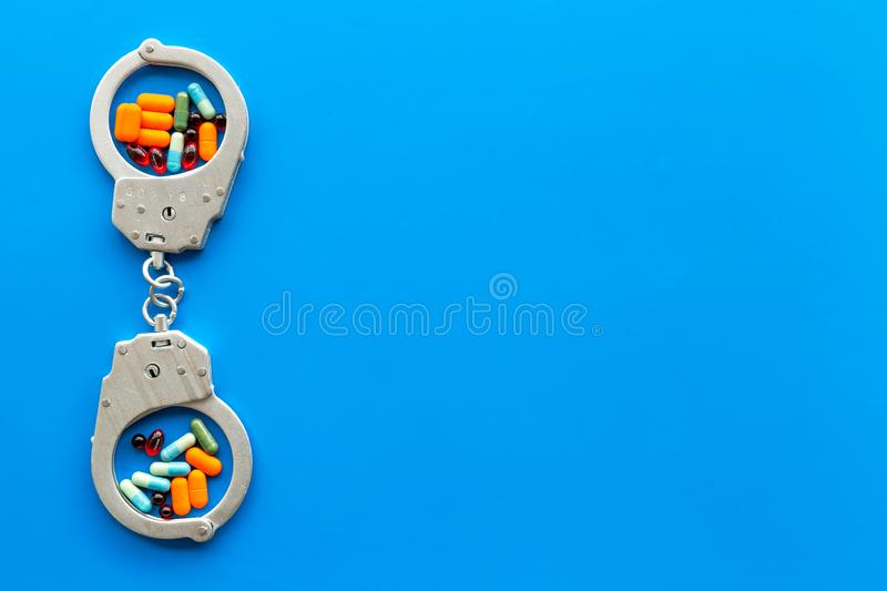 Arrest for illegal purchase, possession and sale drugs concept. Drugs as pills near handcuff on blue background top view.  stock images