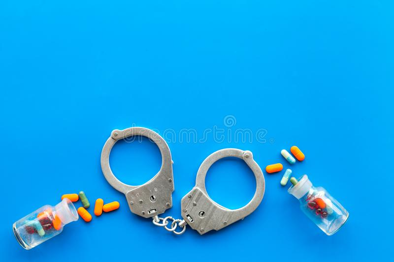 Arrest for illegal purchase, possession and sale drugs concept. Drugs as pills near handcuff on blue background top view.  royalty free stock image
