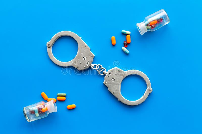 Arrest for illegal purchase, possession and sale drugs concept. Drugs as pills near handcuff on blue background top view.  royalty free stock photo