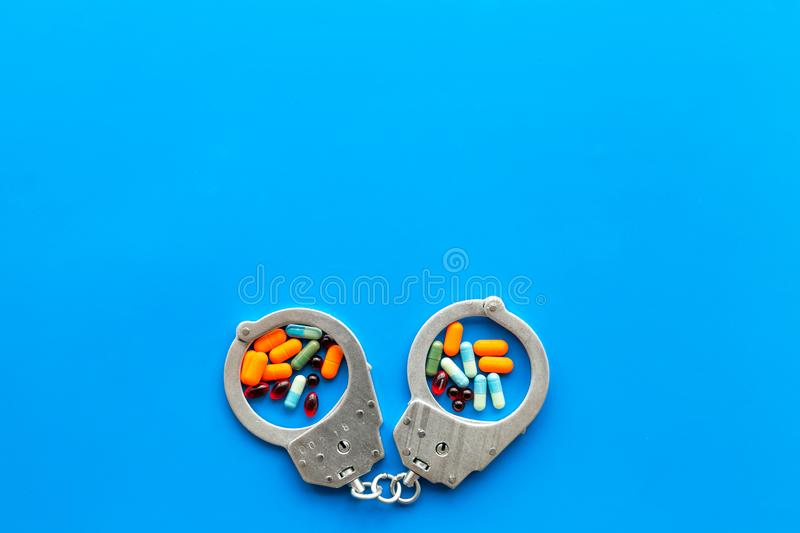 Arrest for illegal purchase, possession and sale drugs concept. Drugs as pills near handcuff on blue background top view.  stock photos