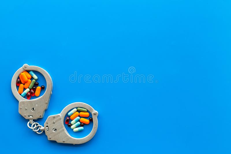 Arrest for illegal purchase, possession and sale drugs concept. Drugs as pills near handcuff on blue background top view.  stock image