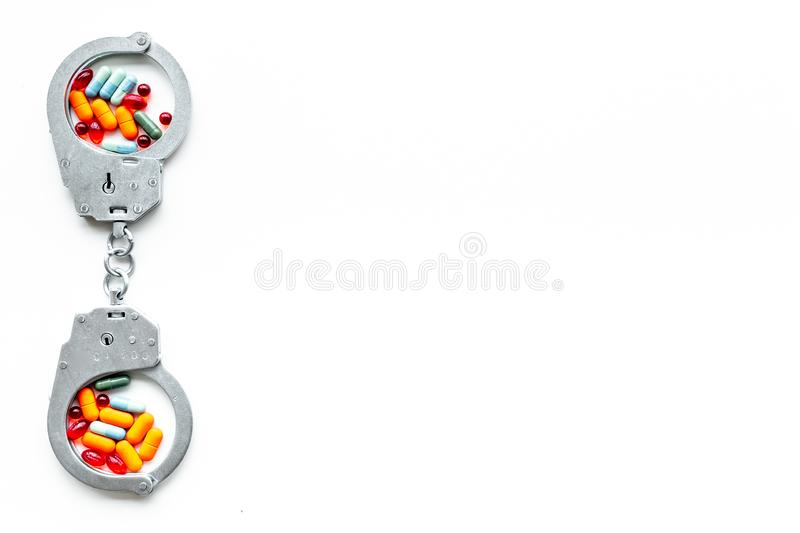 Arrest for illegal purchase, possession and sale drugs concept. Drugs as pills near handcuff on white background top. View royalty free stock photos
