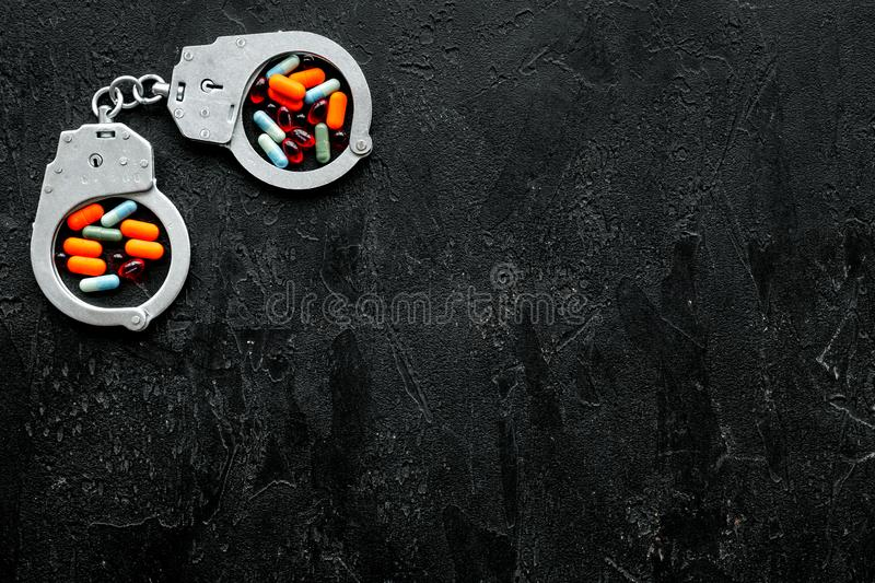 Arrest for illegal purchase, possession and sale drugs concept. Drugs as pills near handcuff on black background top. View royalty free stock images