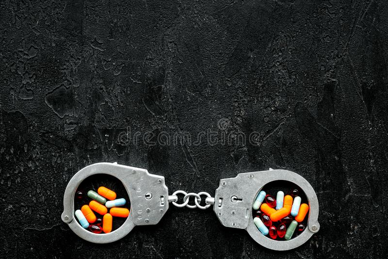 Arrest for illegal purchase, possession and sale drugs concept. Drugs as pills near handcuff on black background top. View stock photography