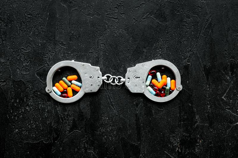 Arrest for illegal purchase, possession and sale drugs concept. Drugs as pills near handcuff on black background top. View royalty free stock photography