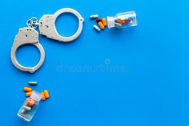 Arrest for illegal purchase, possession and sale drugs concept. Drugs as pills near handcuff on blue background top view.  stock photography