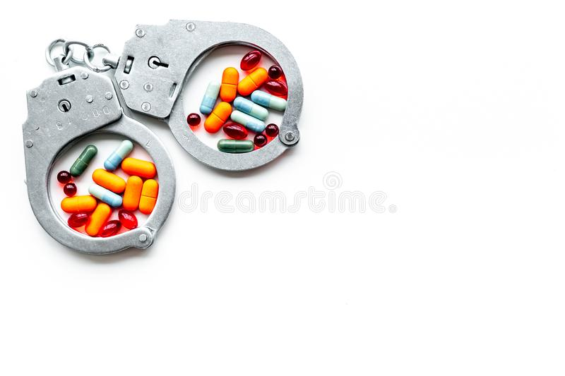 Arrest for illegal purchase, possession and sale drugs concept. Drugs as pills near handcuff on white background top. View royalty free stock photo