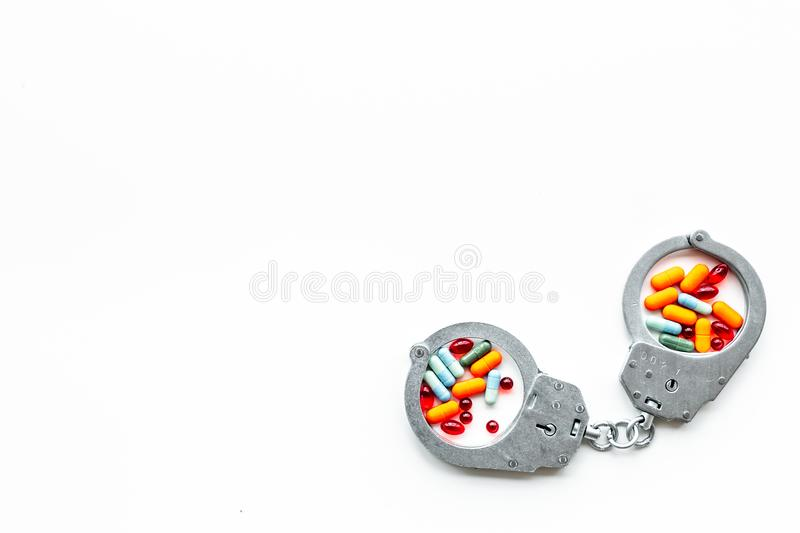 Arrest for illegal purchase, possession and sale drugs concept. Drugs as pills near handcuff on white background top. View royalty free stock image