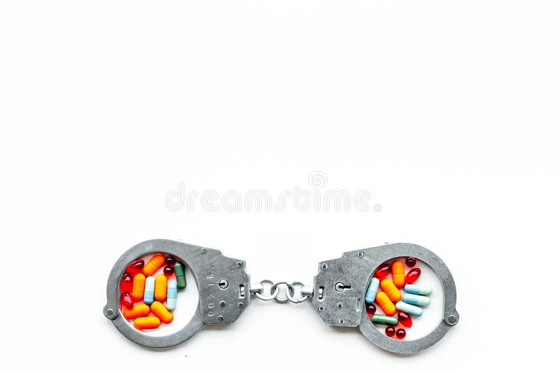 Arrest for illegal purchase, possession and sale drugs concept. Drugs as pills near handcuff on white background top. View royalty free stock photography