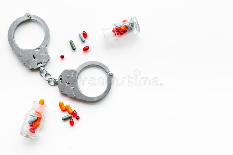 Arrest for illegal purchase, possession and sale drugs concept. Drugs as pills near handcuff on white background top. View stock photography