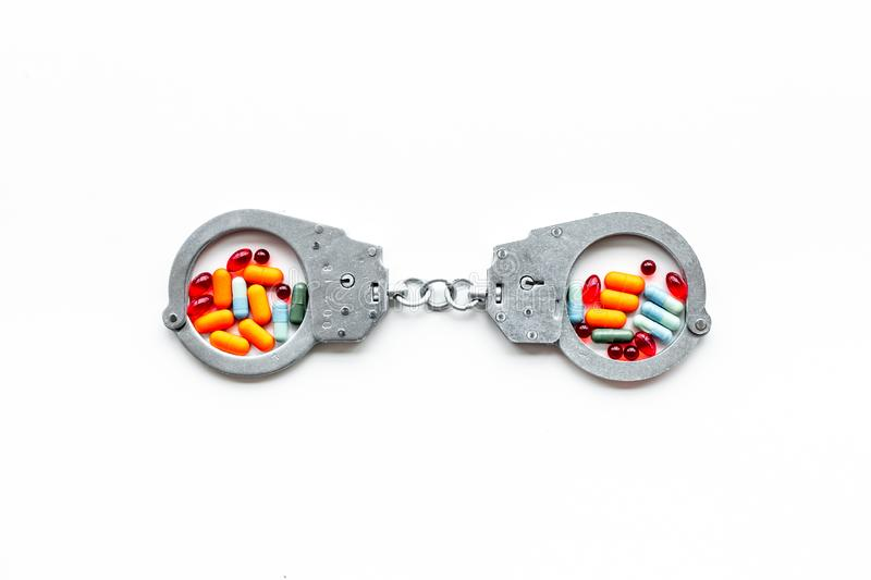 Arrest for illegal purchase, possession and sale drugs concept. Drugs as pills near handcuff on white background top. View stock image