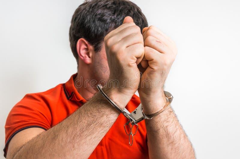 Arrestant in handcuffs verborgen zijn gezicht stock afbeelding
