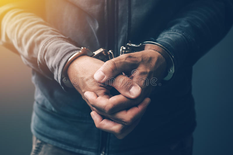 Arrested computer hacker with handcuffs. Arrested computer hacker and cyber criminal with handcuffs, close up of hands stock photos