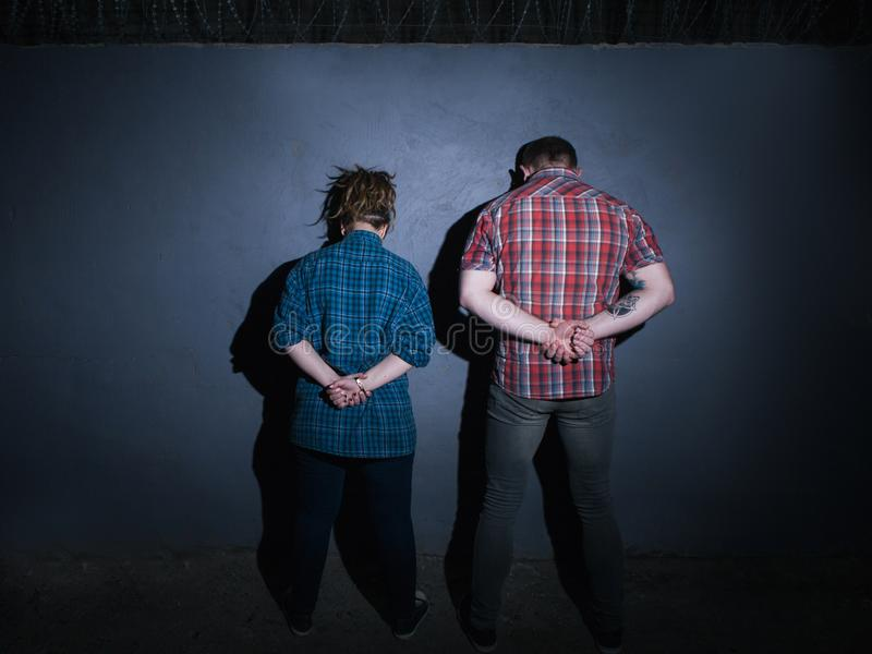 Arrested criminal couple. Partners in crime. Detained unrecognizable people at night on blue background, youth with hands behind back, prison concept royalty free stock images