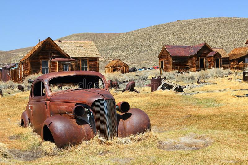 Arrested Decay at Bodie State Historic Site, California. An abandoned car, old wooden houses, and a range of gold mining equipment mark the site of Bodie ghost royalty free stock image