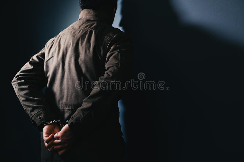 Arrested male criminal with handcuffs facing prison wall. As copy space royalty free stock photos