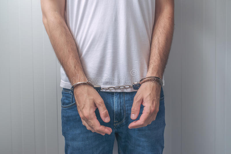 Arrested man with cuffed hands in front. Arrested man with cuffed hands. Unrecognizable male person in jeans with handcuffs held in police station for being stock photo