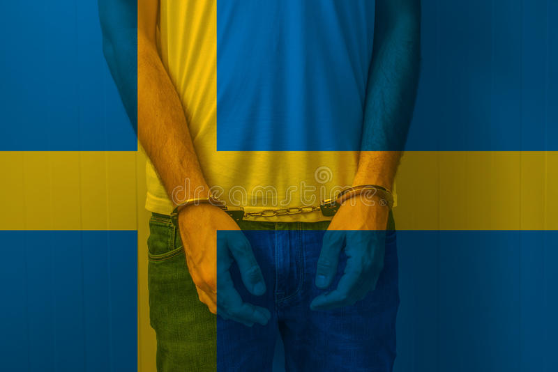 Arrested man with cuffed hands wearing shirt with Swedish flag. Unrecognizable male person in jeans with handcuffs held in police station for being suspected stock photos