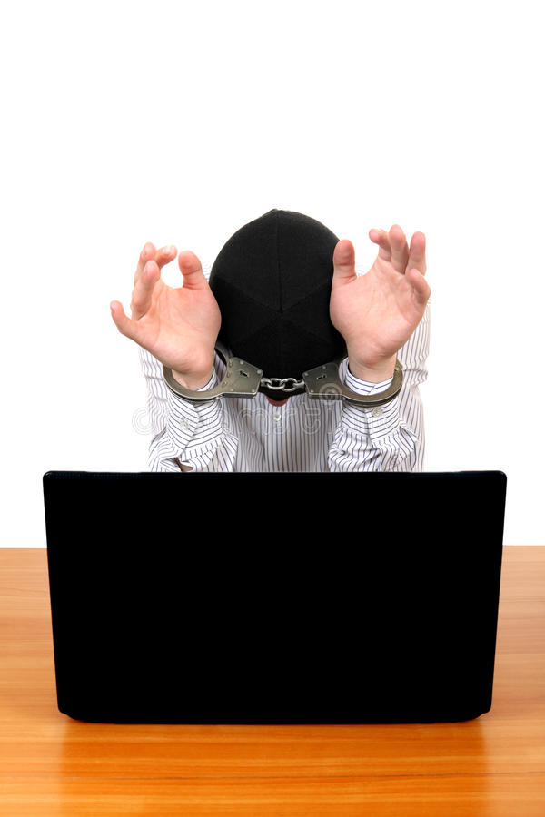 Arrested Man with Laptop. Arrested Man in Handcuffs at the Desk with Laptop Isolated on the White Background royalty free stock images