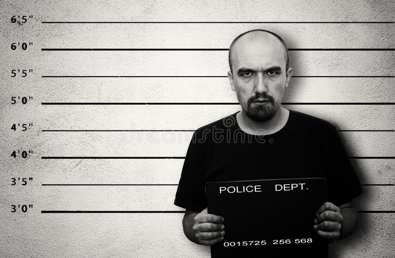 Arrested. Police mugshot of arrested criminal. Black and white image with copy space royalty free stock image