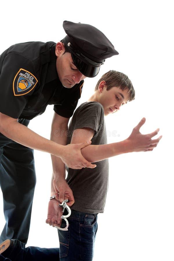 Arresterende de tienermisdadiger van de politieagent royalty-vrije stock fotografie