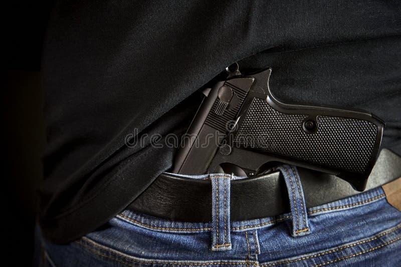 Arrière caché d'arme à feu à l'homme dans des blues-jean image stock