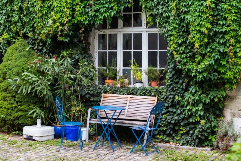 Arrière-cour gentille avec les fleurs roses, table, chaises Conception de paysage, image libre de droits