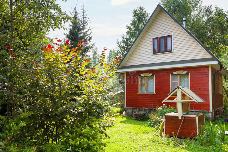 Arrière-cour verte de cottage de pays avec le puits photo libre de droits