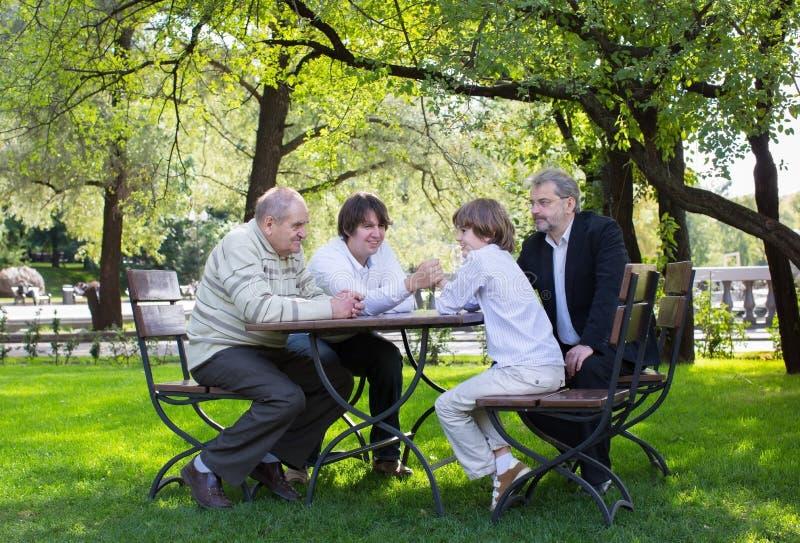Arrière-grand-père, grand-père, père et fils luttant à une table en bois en parc photographie stock