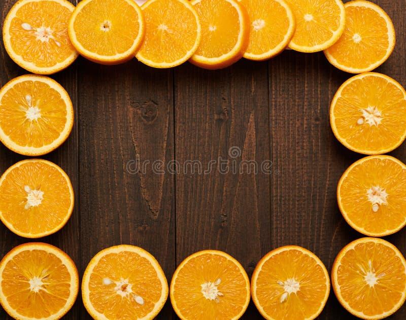 Arrière-plan en bois foncé avec espace vide pour le texte et cadre de fruits frais coupés en tranches d'orange - nourriture natur photo stock