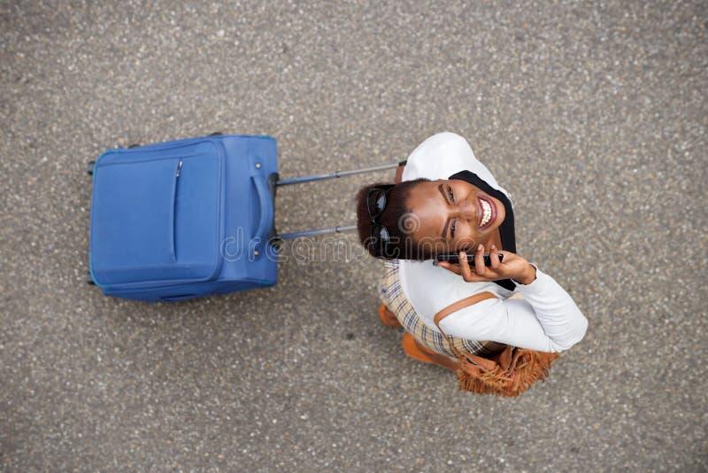 Arriba de la mujer afroamericana feliz que camina con el bolso del viaje y el teléfono móvil fotografía de archivo libre de regalías