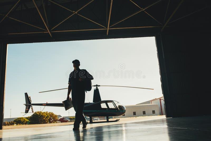 Arrivée pilote d'hélicoptère au hangar d'avion image stock