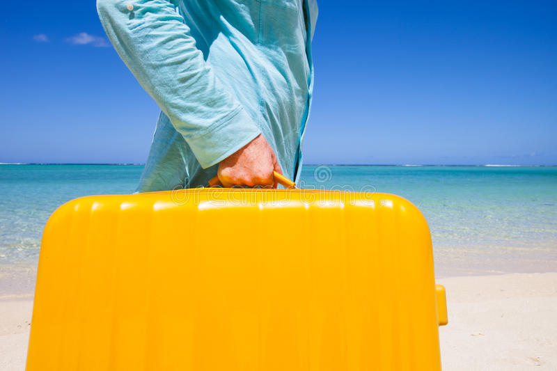 Arrival at the beach II. Travel background with a person carrying a yellow suitcase at a white sandy beach with a turquoise sea and a blue sky, concept for royalty free stock images