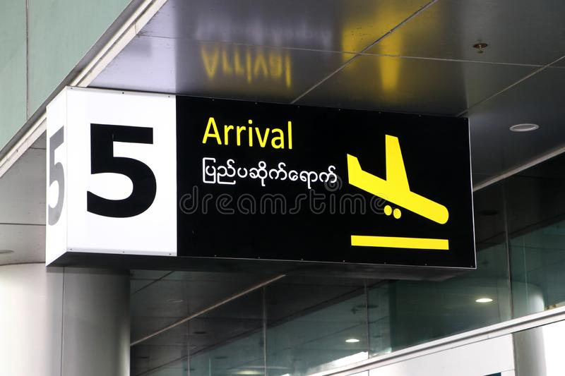 Arrival sign in english and Myanmar language with symbol of the plane landing in yellow on black color at the gate number 5 royalty free stock photos