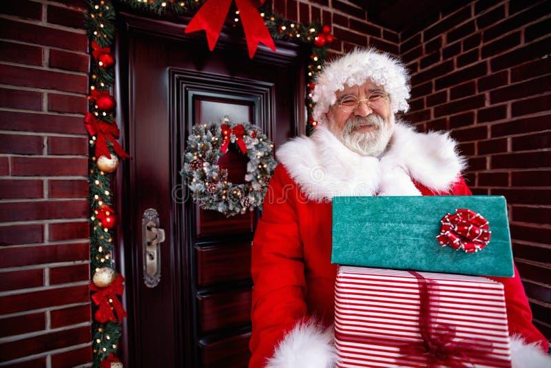 Arrives Santa Claus sonriente y regalo de la Navidad de las porciones que lleva imagen de archivo libre de regalías