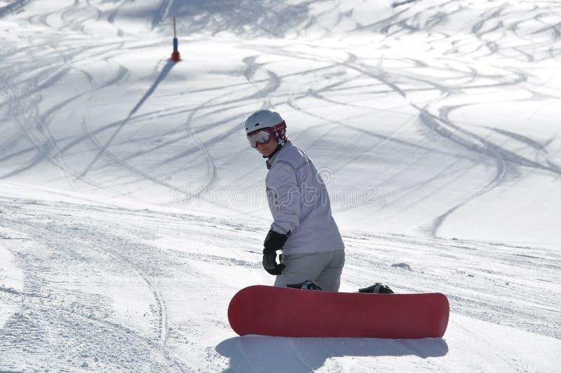 Arrodillamiento femenino del snowboarder imagen de archivo libre de regalías