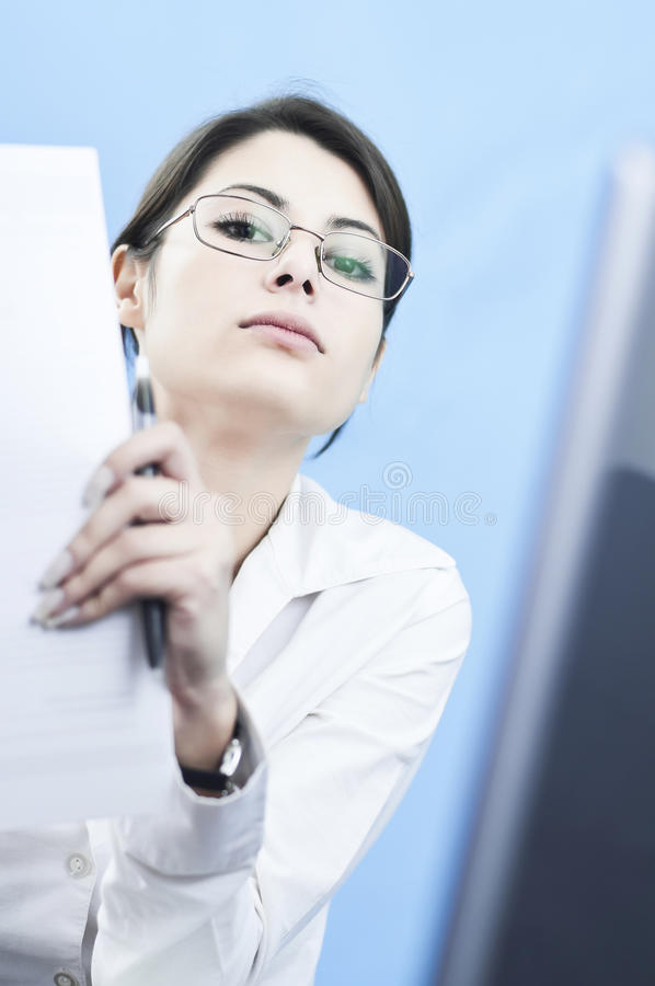 Arrogant business woman. Getting ready to read something from a paper with a computer in the background, focus selected on the expressive face royalty free stock images