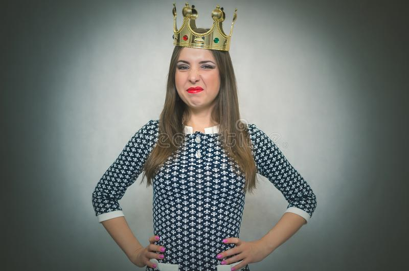 Arrogant disgruntled woman with golden crown. Selfish woman. Selfish woman. Arrogant disgruntled girl with high self esteem. Egoist person woman with golden stock photos