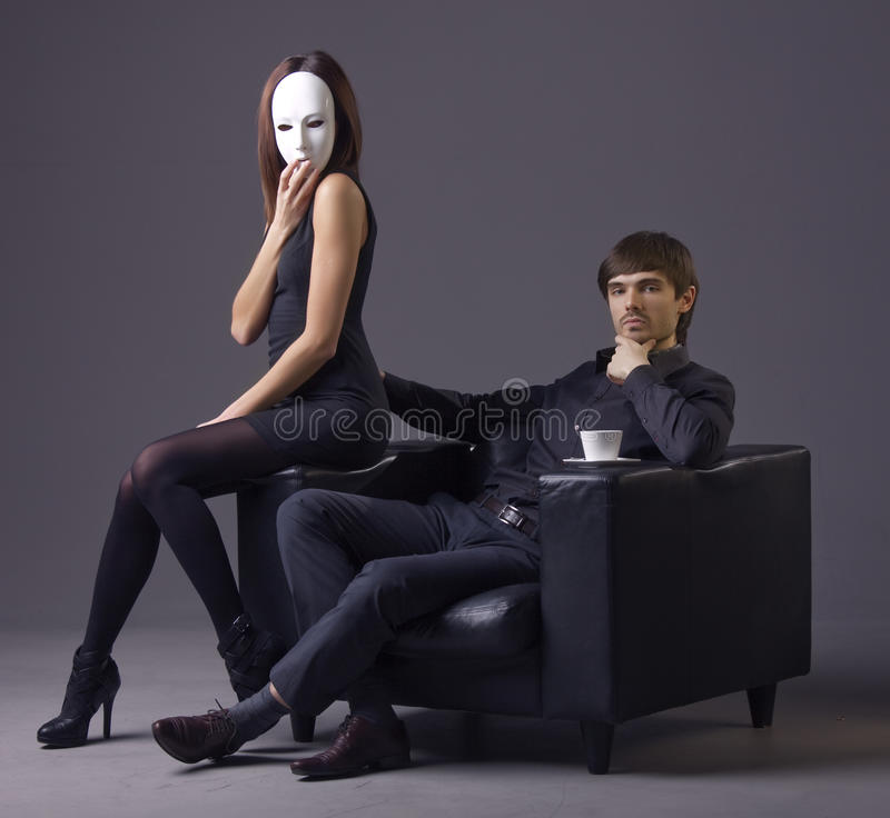 Arrogant man and masked woman. Sitting in the chair over grey background royalty free stock photos
