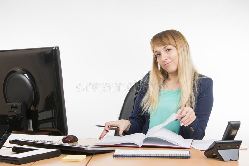 Arrogant office a specialist office leafing through a book and looking at the frame. Young woman secretary sitting at office desk working, isolated on white royalty free stock photo