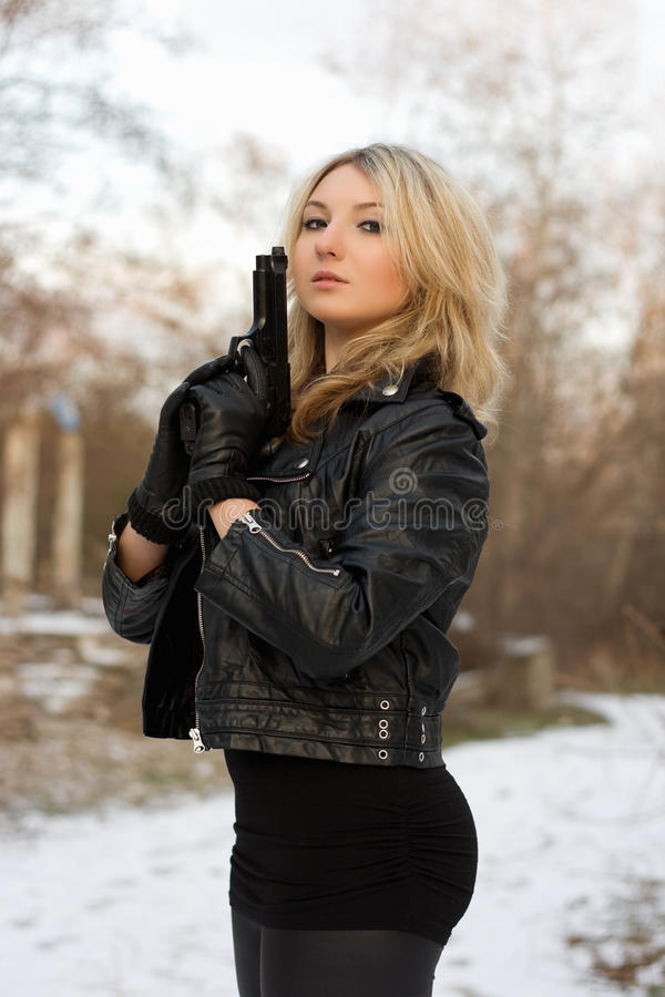 Arrogant pretty woman. With a gun in winter forest royalty free stock photo