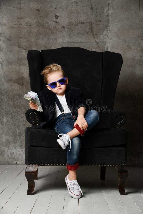 Free Arrogant Rich Boy Kid Millionaire Sits With Crossed Legs In Big Luxury Armchair And Hands Us A  Bundle Wad Of Money Dollars Cash Royalty Free Stock Photos - 150005828