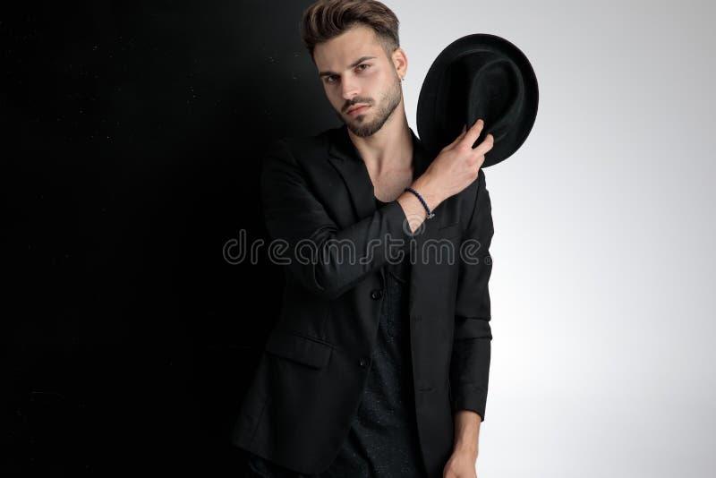 Arrogant smart casual man holding hat on shoulder in studio royalty free stock photo