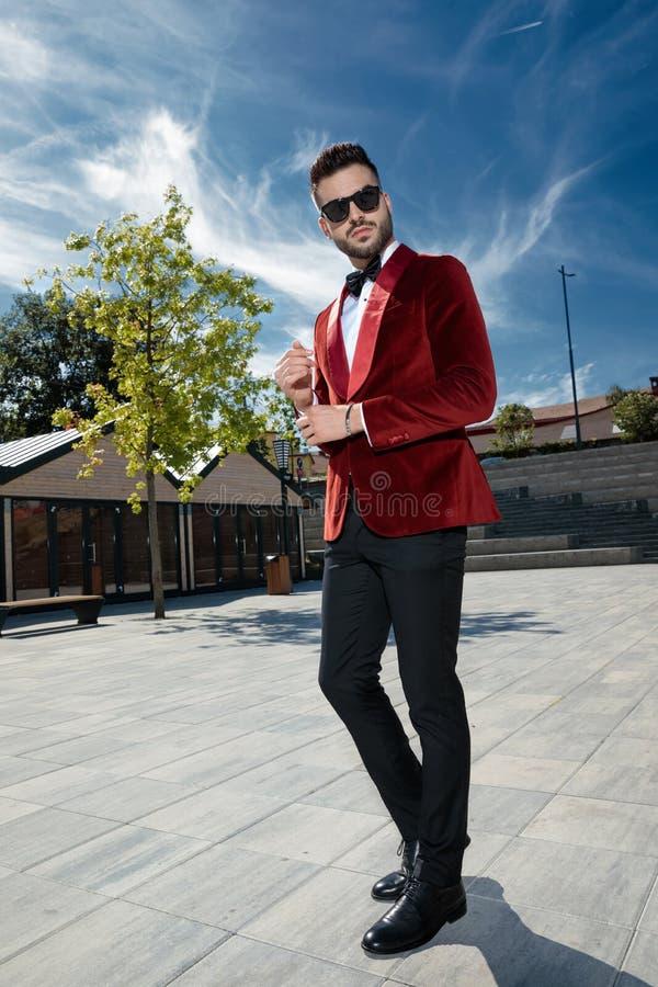 Arrogant young elegant man adjusting sleeve outdoor stock images