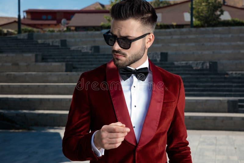 Arrogant young elegant man wearing red velvet tuxedo outdoor stock images