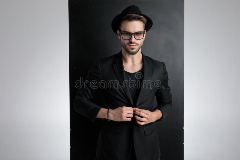 Arrogant young man arranging black coat in studio royalty free stock photos