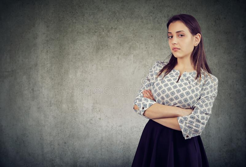 Arrogant young woman with arms crossed. Young haughty woman looking overconfident while standing with arms crossed on gray background stock photo