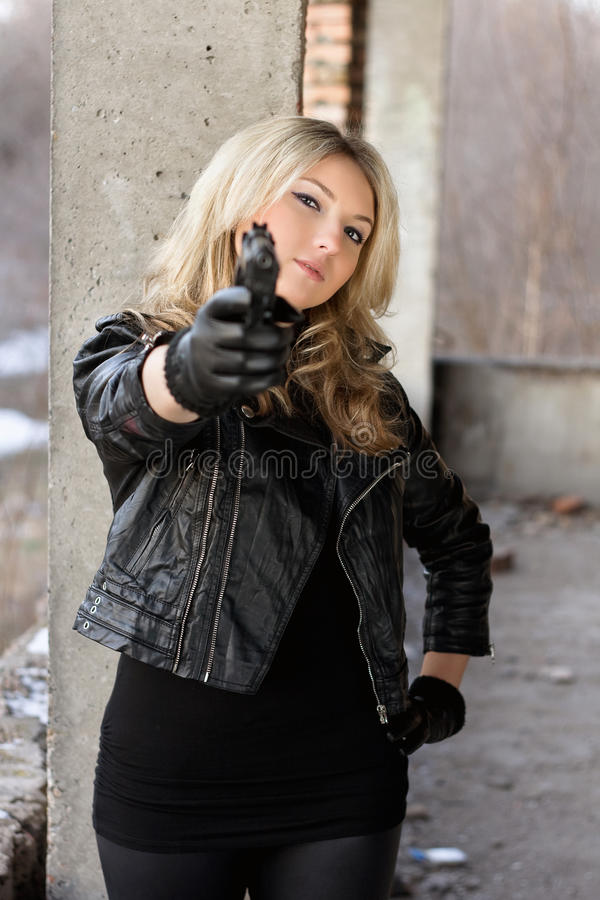 Arrogant young woman with a gun. Arrogant young woman in leather jacket with a gun stock photo
