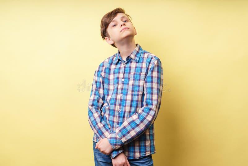 Arroganter hochmütiger überzeugter Junge am gelben Hintergrund stockfotografie